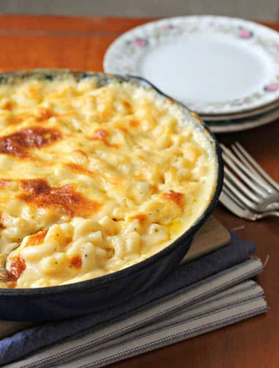 a skillet of baked macaroni and cheese on a table with plates and forks