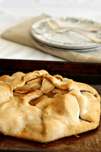 apple pie with plates and forks on a table