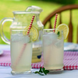 two glasses of lemonade with a pitcher of lemonade on a table
