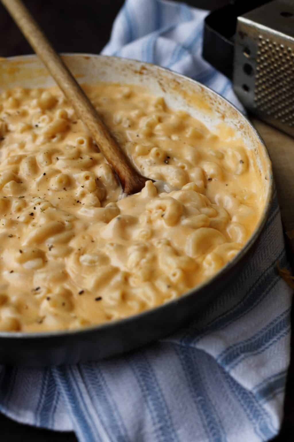 one pot macaroni and cheese in a skillet with a wooden spoon