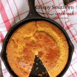 baked cornbread in a cast iron skillet on a red napkin