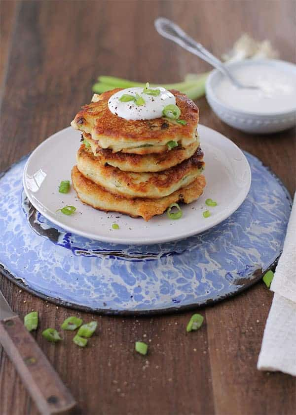 a stack of crispy potato cakes with sour cream on top on a small white plate on a blue dish