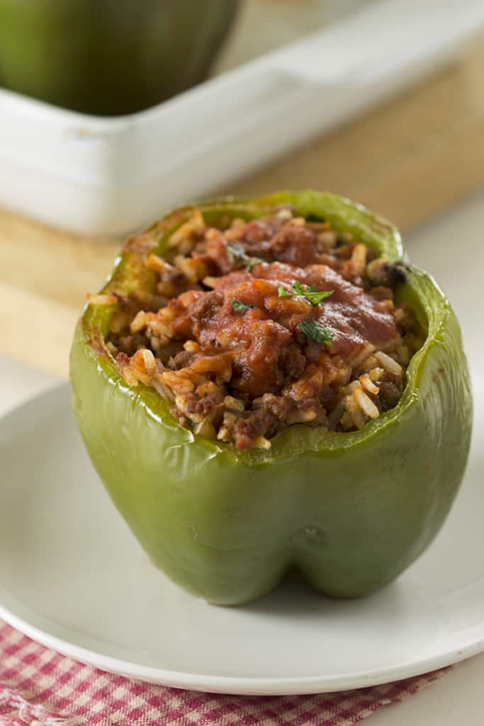 one green stuffed pepper on a small white plate on a red napkin