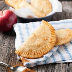 two fried apple pies on a blue napkin