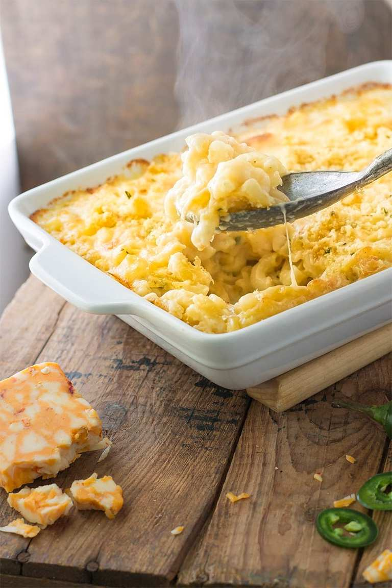 a white baking dish of spicy baked mac and cheese on a wooden table with sliced jalapenos and a block of cheese on the side