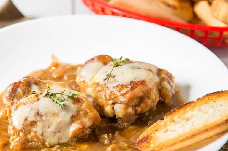 french onion chicken on a white plate with a bread stick