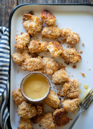 a platter of baked chicken nuggets with honey mustard and a fork