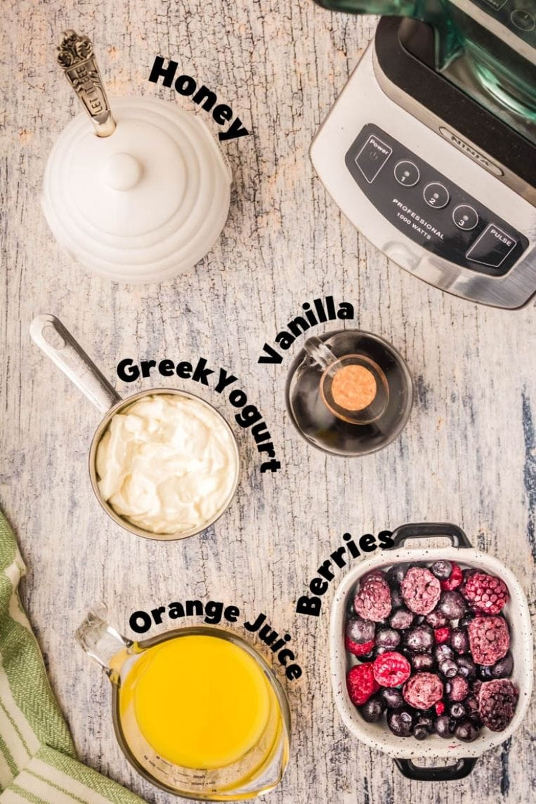 a table with the ingredients for making a smoothie laid out individually and labeled . Honey, vanilla, Greek yogurt, orange juice.