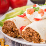two burritos on a plate with filling exposed