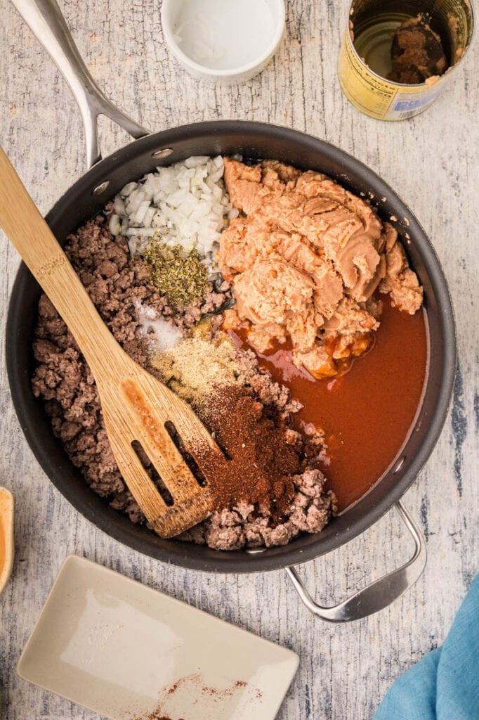 a skillet with browned ground beef, spices, refried beans ready to be stirred together.