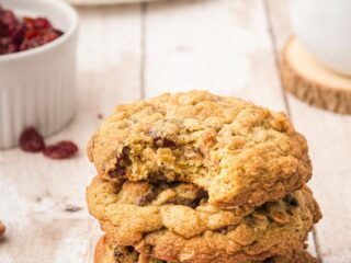 Three stacked breakfast cookies on a table with the top cookie having a bite out of it.