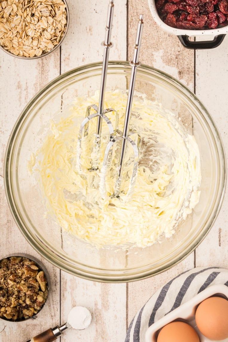 a bowl of butter beaten with a hand mixer