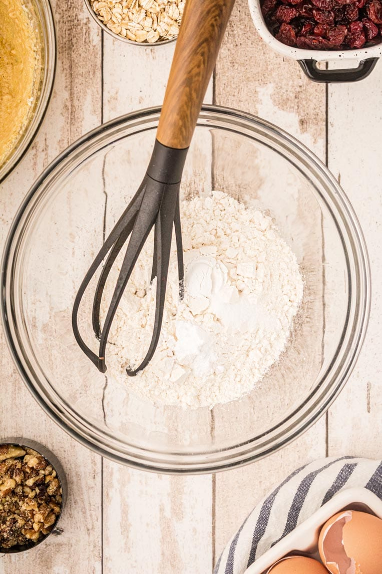 A bowl of flour, baking powder, baking soda and salt with a whisk.