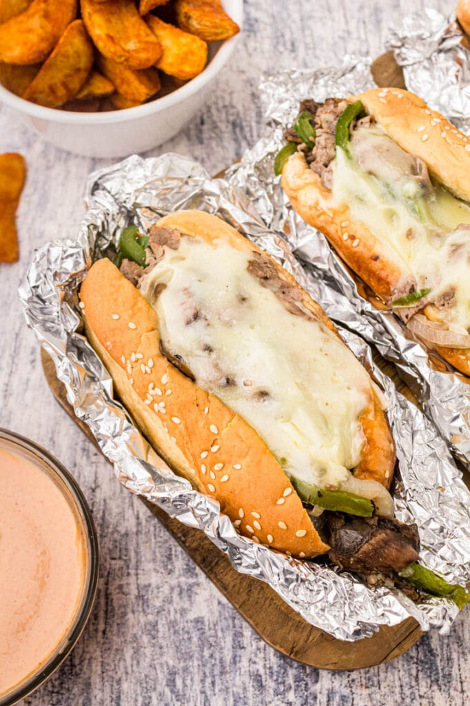 a philly cheesesteak in foil with melted cheese