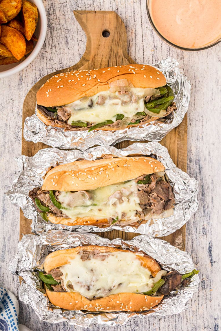 Three Philly cheese steaks wrapped in foil on a cutting board.