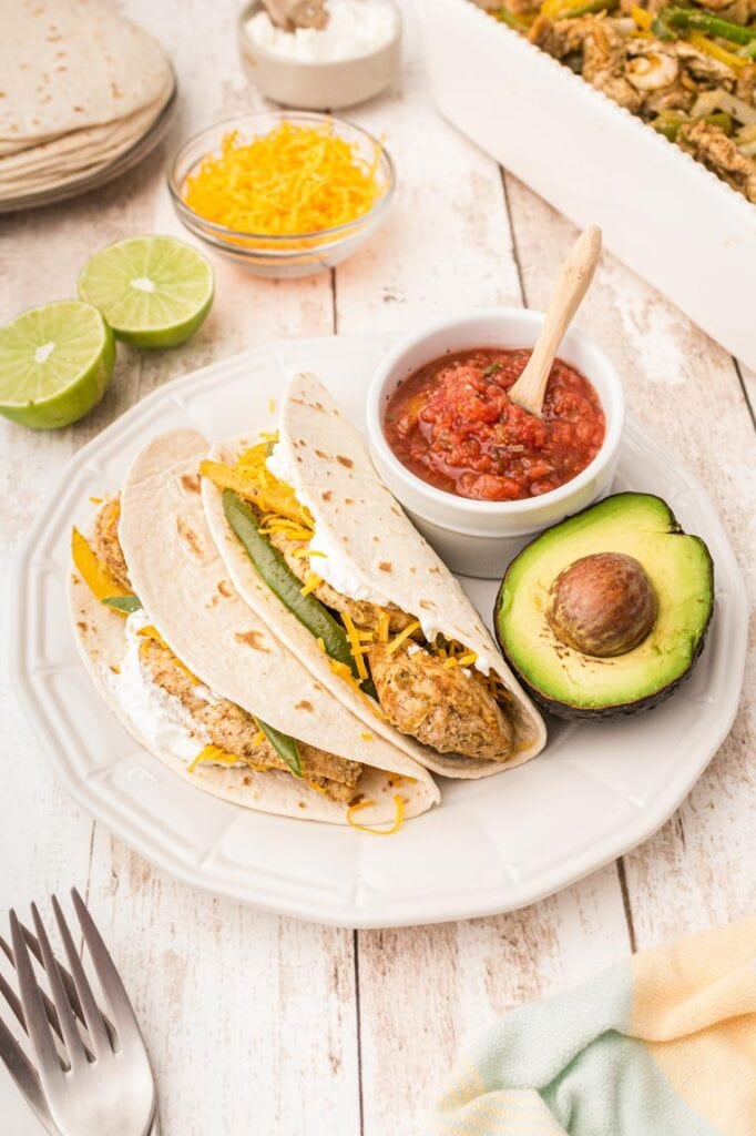 A plate of two chicken fajitas inside tortillas with salsa, avocado, and limes on a table.