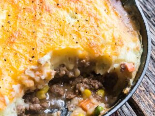 a skillet of cottage pie with a scoop out
