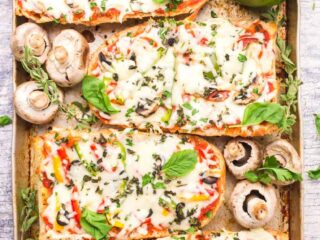 A pan of baked French bread pizzas with vegetables and fresh herbs surrounding them.
