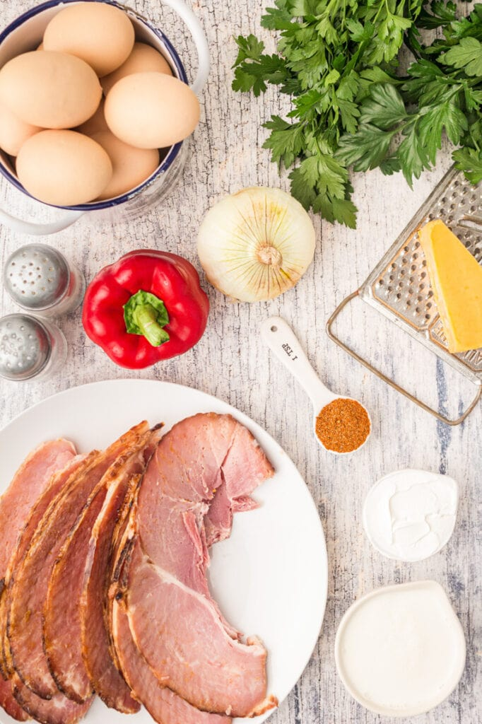 Ham, eggs, bell peppers, cheese, and spices for egg cups assembled on a table.