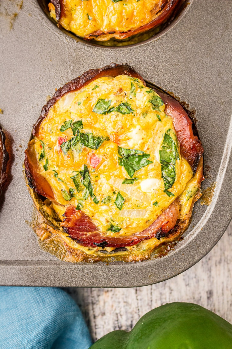a close up of baked egg muffins in a tin
