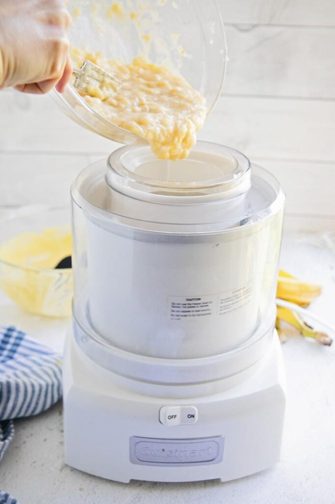 a bowl of mashed bananas being added to ice cream while churning