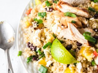 a white platter of Mexican quinoa salad with a spoon on the side.