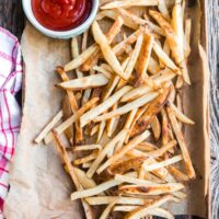 a cookie sheet of baked fries with ketchup