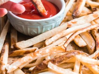a hand dipping a fry in ketchup