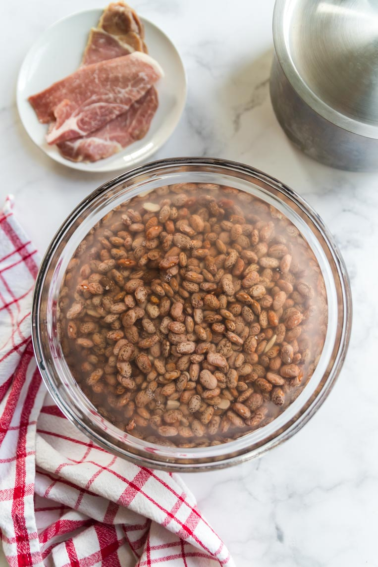 a bowl of pinto beans soaking in water