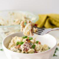 a white bowl of potato salad with a fork holding up a potato