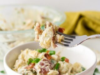 a white bowl of potato salad with a fork holding up a potato