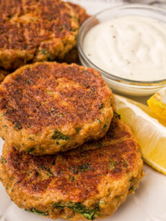 salmon patties on a plate with lemons and sauce