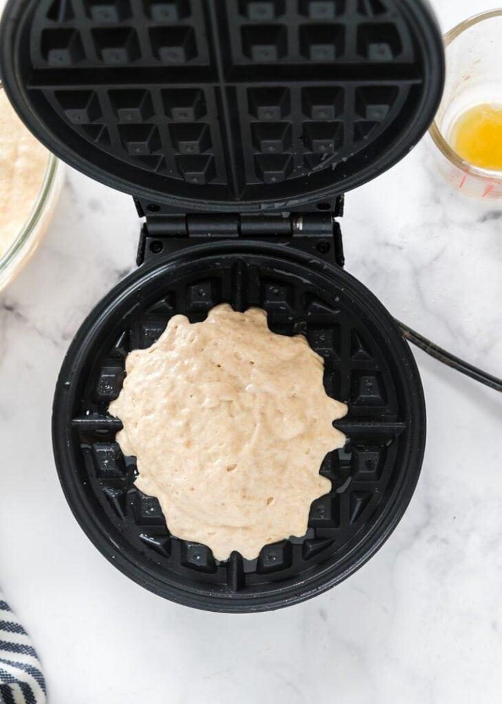 mixed waffle batter on a waffle iron.