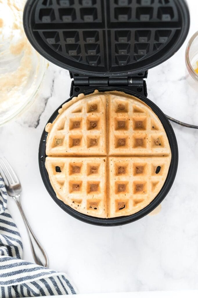 A cooked waffle inside the waffle iron with the lid up looking down on the waffle from above.