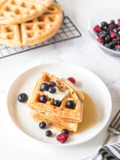 three triangular waffles on a white plate with butter and berries
