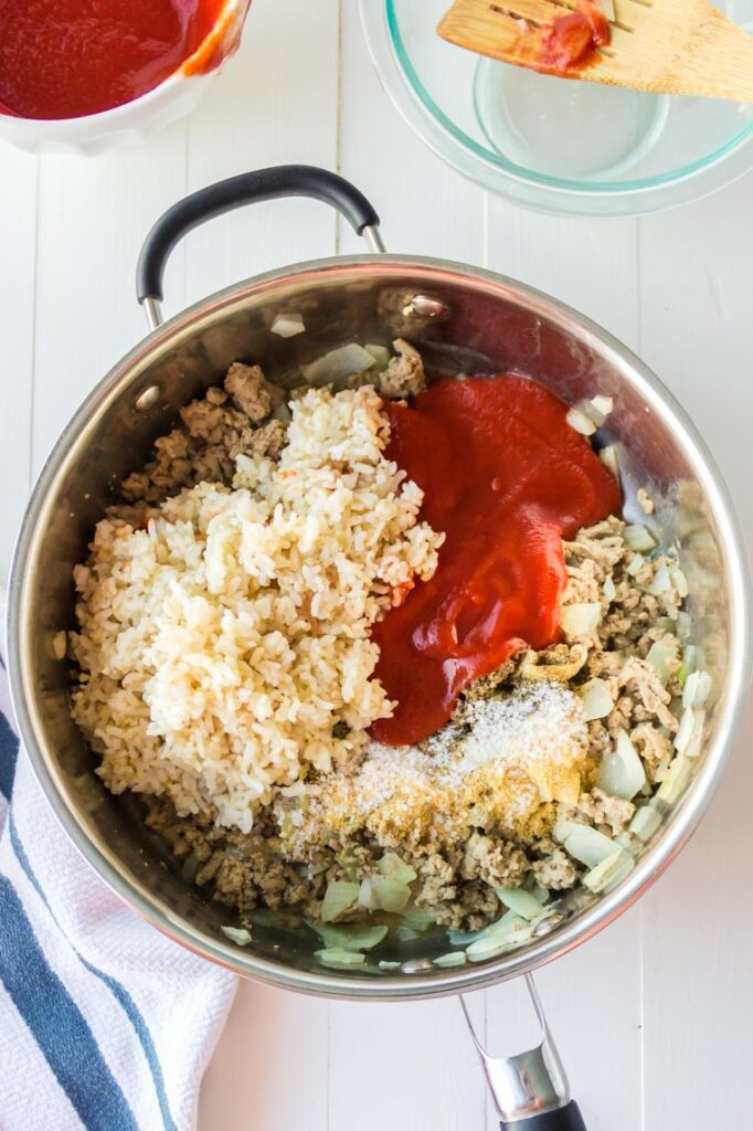 a skillet with rice, tomato sauce and cooked pepper fillings