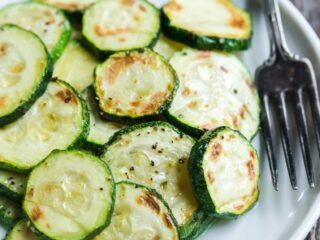 a plate of roasted zucchini slices on a plate with a fork