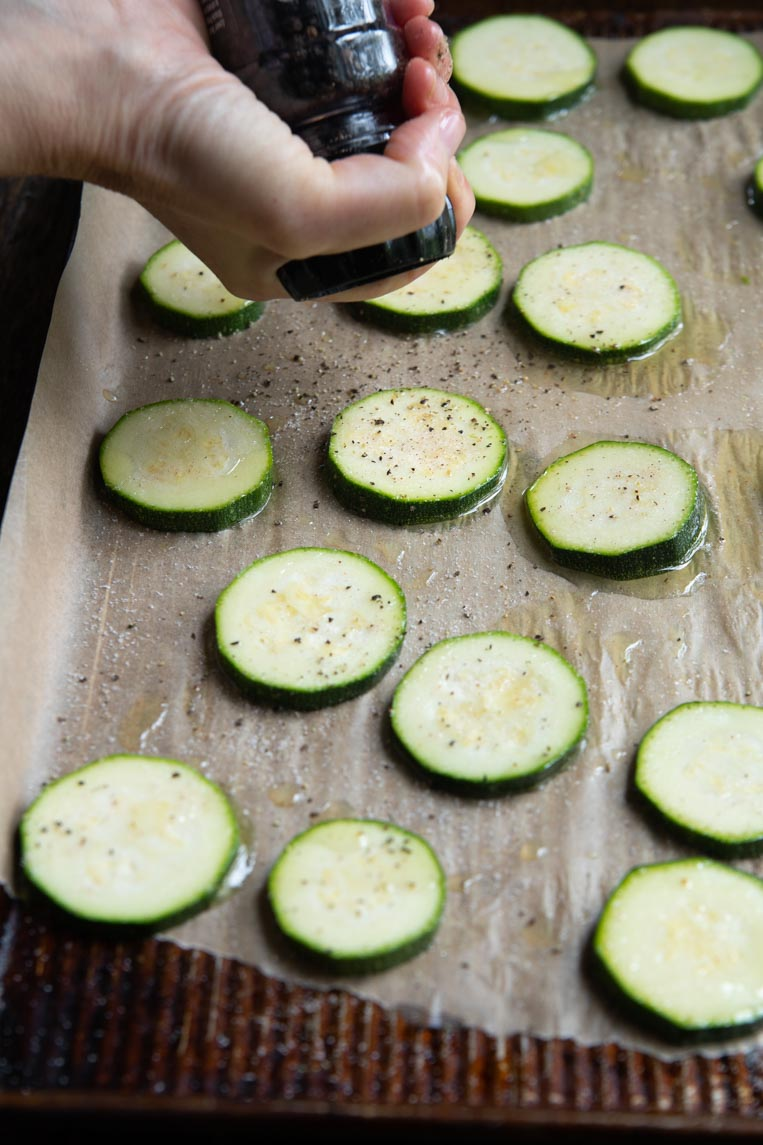 black pepper being ground over zucchini slices