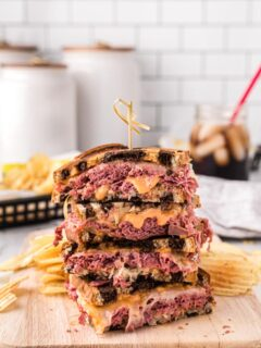 a stack of reuben sandwiches on a cutting board