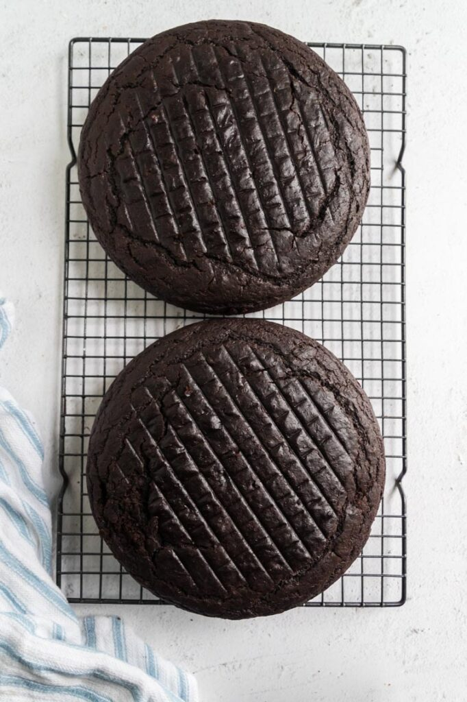 two baked chocolate cake rounds on a cooling rack