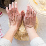 two hands gently pressing the dough away from the body.