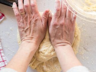 Two hands using the heel of the hands to press into the dough