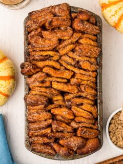 a baked loaf of pull apart bread with pumpkin on a white table