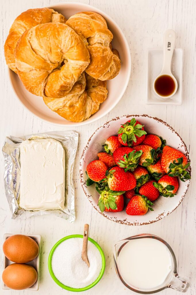A table with ingredients for strawberry croissant breakfast bake.
