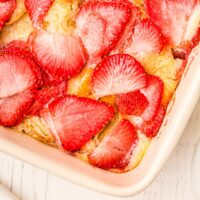 corner of a baking dish overlooking strawberries on top of casserole