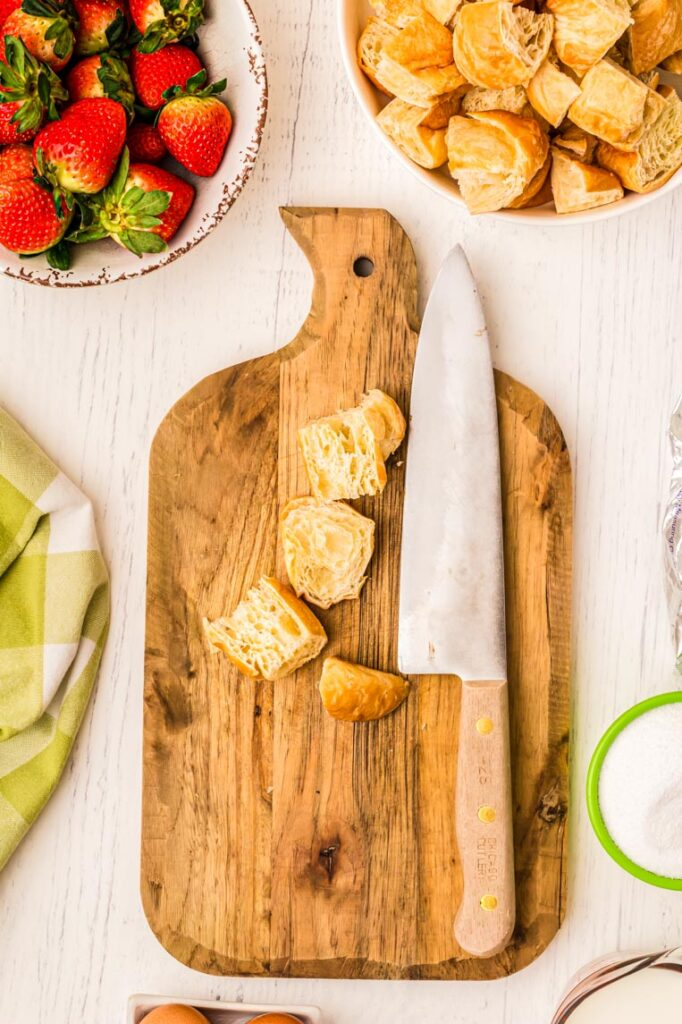 A cutting board, knife on a table with four cut up croissant pieces.
