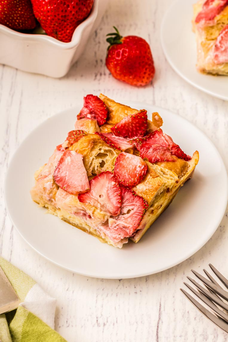 A slice of strawberry croissant breakfast casserole on a plate