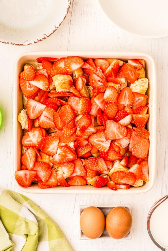 An 8 by 8 baking dish with croissants filling the pan, and sliced strawberries layered on top.