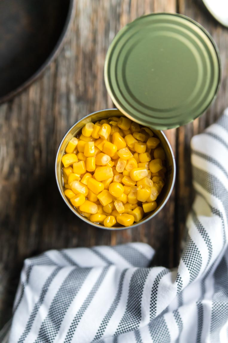 a can of corn open with the lid peeled back on a table