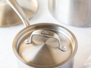 three stainless steel cookware pieces on a table